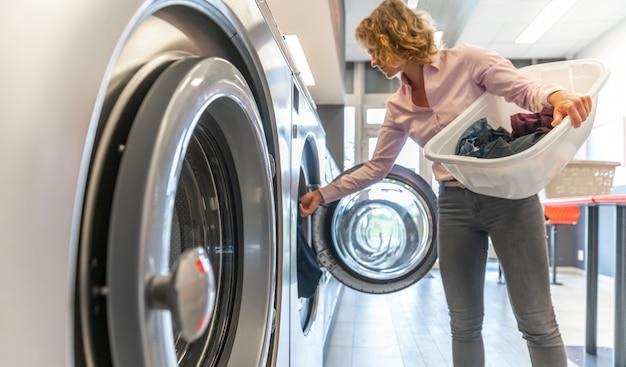 Frau, die schmutzige kleidung in die waschmaschine im waschraum einführt