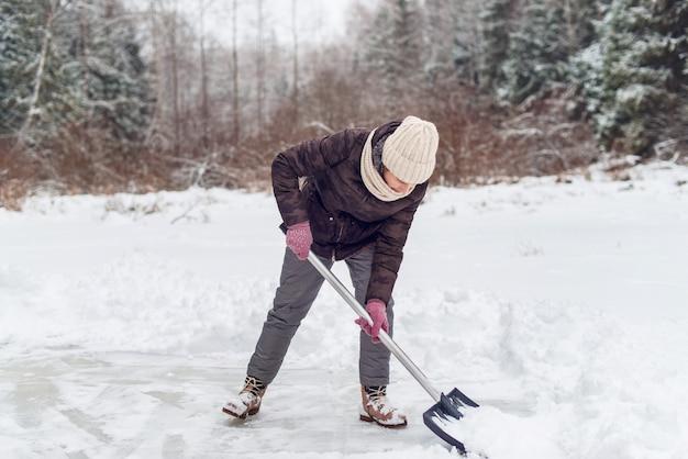 Frau, die schnee mit einer schaufel im winter entfernt.