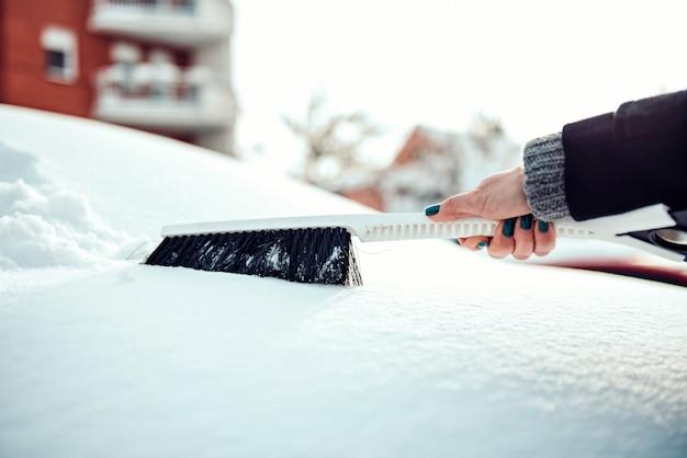 Frau, die schnee vom auto entfernt