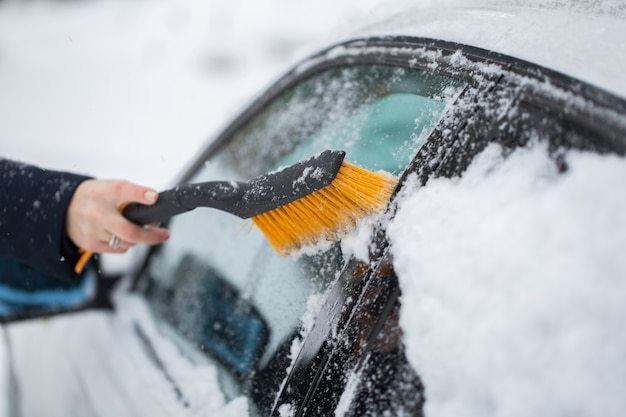 Frau, die schnee vom auto im winter reinigt