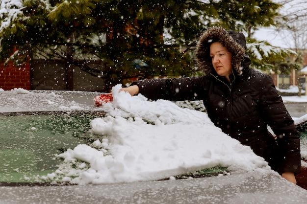 Frau, die schnee von der windschutzscheibe des autos auf einem parkplatz nach einem winterschneesturm entfernt