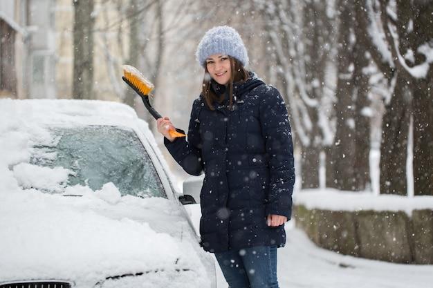 Frau, die schnee von der windschutzscheibe des autos entfernt