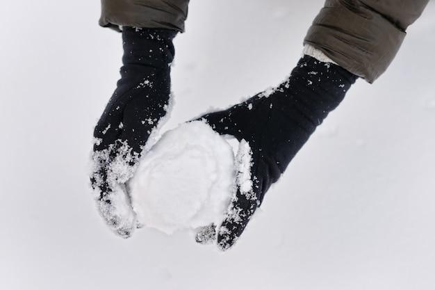 Frau, die schneeball in ihren händen hält