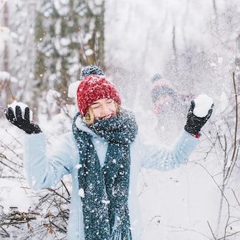 Frau, die schneeballspiel im wald verliert