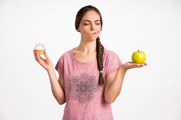 Frau, die schnelles oder gesundes lebensmittel wählt