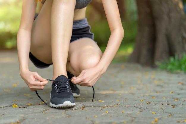 Frau, die schnürsenkel bindet. weiblicher sporteignungsläufer, der zum rütteln am garten fertig wird.