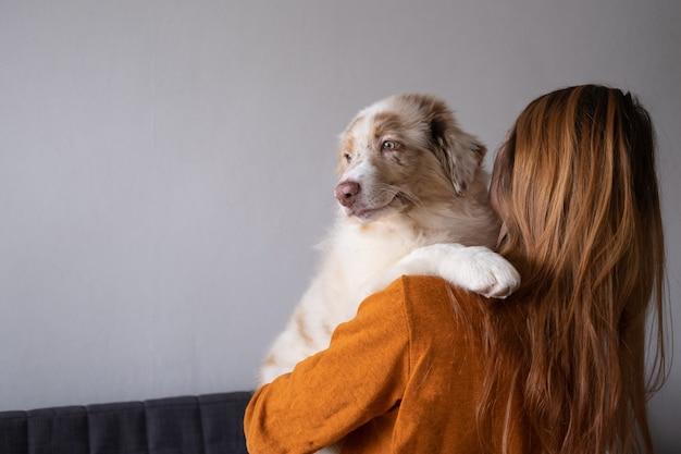 Frau, die schönen kleinen niedlichen australischen schäferhund rot merle welpenhund umarmt. beste freunde. liebe und freundschaft zwischen mensch und tier. vier monate.