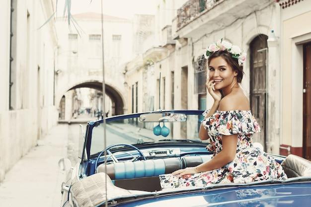 Frau, die schönes kleid und retro-cabrioauto an der stadt havanna trägt