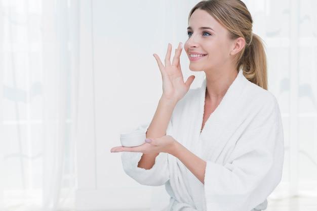 Frau, die schönheitscreme in einem badekurort verwendet