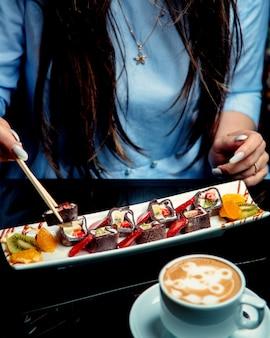 Frau, die schokoladen-crêpe-rollen mit erdbeer-bananen-kiwis mit stäbchen gefüllt nimmt