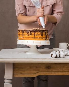 Frau, die schokoladencreme auf kuchen zusammendrückt