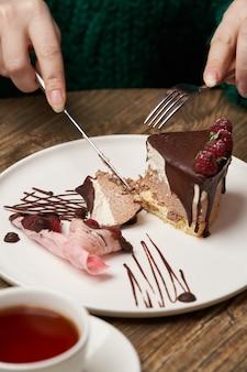 Frau, die schokoladenkuchen mit himbeere isst. frauenhände, die schokoladenmoussekuchen mit himbeere schneiden