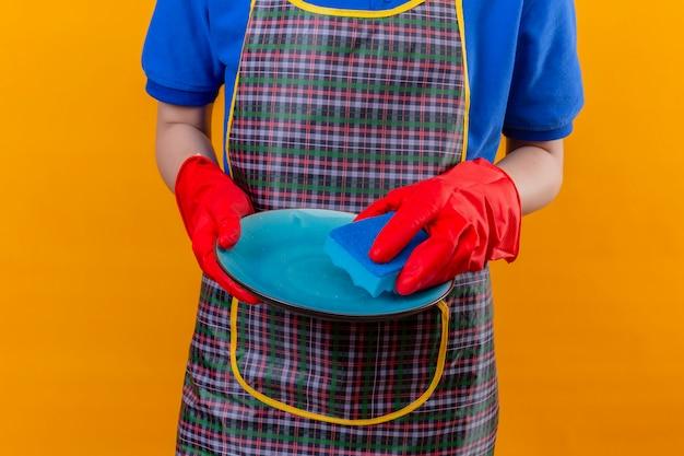 Frau, die schürze und gummihandschuhe trägt, die geschirr in den händen halten, waschteller über orange wand