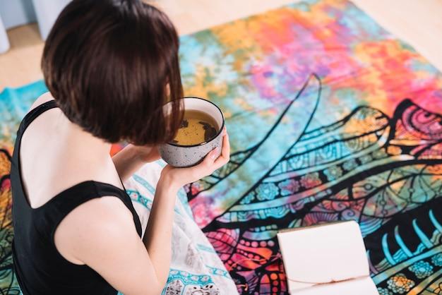 Frau, die schüssel gesunde suppe während des yoga hält