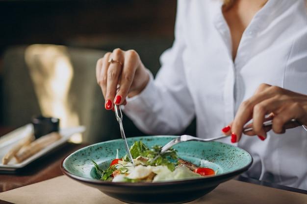 Frau, die schüssel salat isst