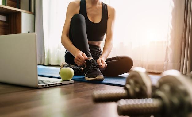 Frau, die schuhe bindet. eine person, die im trainingsanzug läuft und ihre schnürsenkel im fitnessstudio bindet