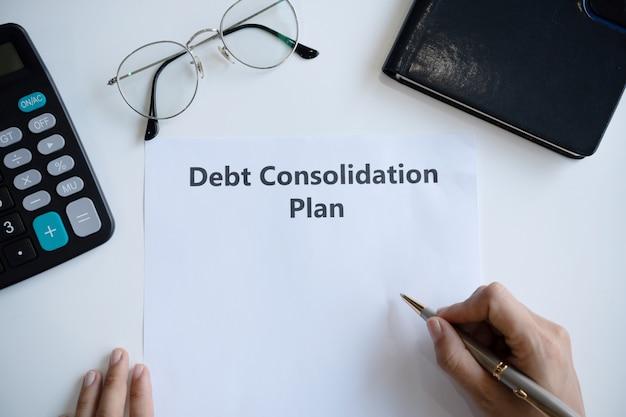 Frau, die schuldenkonsolidierungsplan in papier auf schreibtisch schreibt. speicherplatz kopieren, draufsicht.