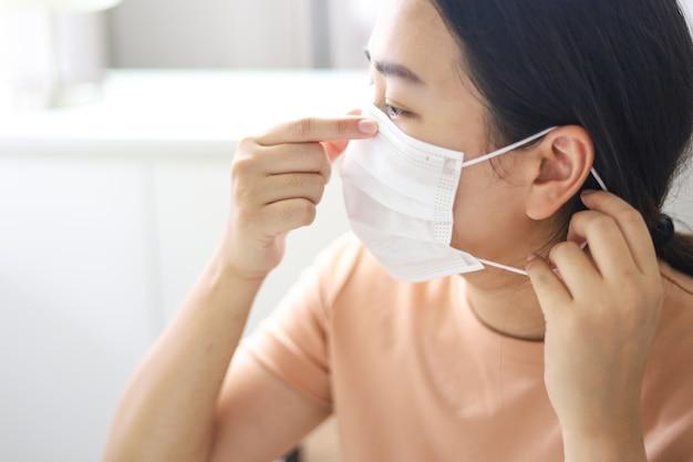 Frau, die schutzgesichtsmaske gegen coronavirus trägt