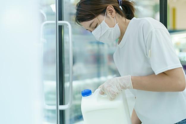 Frau, die schutzmaske beim einkaufen im supermarkt trägt, trägt flasche milch, panik, die lebensmittel kauft. angst vor coronavirus.