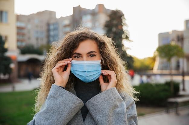 Frau, die schutzmaske gegen coronavirus trägt. coronavirus covid-19 pandemie- und gesundheitskonzept. coronavirus vorsichtsmaßnahmen