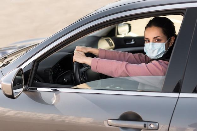 Frau, die schutzmaske im auto trägt