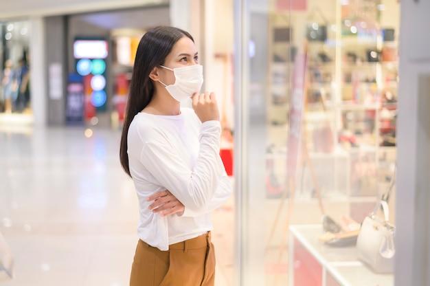 Frau, die schutzmaske trägt, die unter covid-19-pandemie im einkaufszentrum einkauft