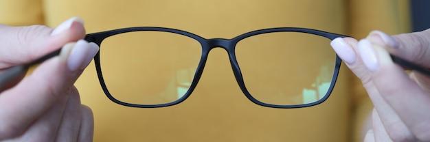 Frau, die schwarze brillen in ihren armen nahaufnahme hält