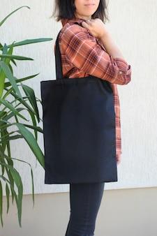 Frau, die schwarze einkaufstasche hält