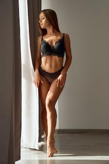 Frau, die schwarze unterwäsche trägt, die nahe schlafzimmerfenster aufwirft