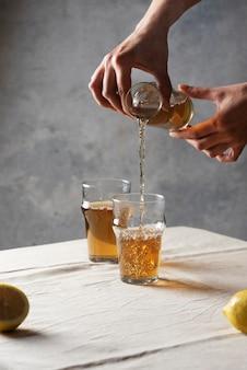 Frau, die schwarzen heißen tee in ein glas, selektives fokusbild im minimalismusstil gießt