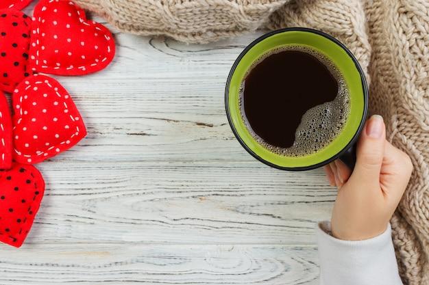 Frau, die schwarzen kaffee mit roten herzen und beige strickjacke trinkt