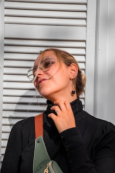 Frau, die schwarzen rollkragenpullover und gürteltasche trägt