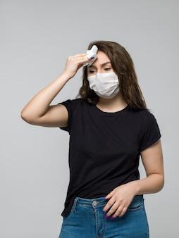 Frau, die schwarzes t-shirt und medizinische schutzmaske trägt, die sich krank fühlen
