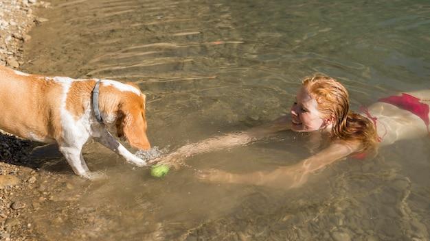 Frau, die schwimmt und mit hoher sicht des hundes spielt