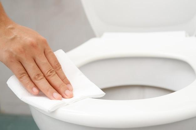 Frau, die seidenpapier verwendet, säubert die toilette im badezimmer zu hause.