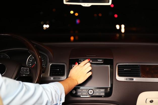 Frau, die sein modernes auto nachts in der stadt, nahaufnahme fährt