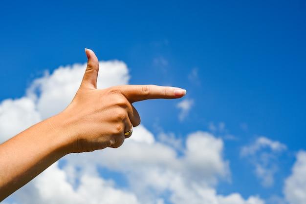 Frau, die seine hand und wolkenhimmel zeigt