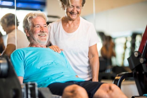 Frau, die seinem mann im fitnessstudio hilft, mit seinen beinen zu trainieren - aktives rentnerpaar, das zusammen übungen macht - gesunder lebensstil