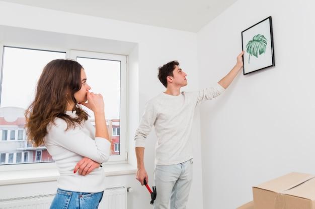 Frau, die seinen freund betrachtet, der den bilderrahmen auf weißer wand hängt
