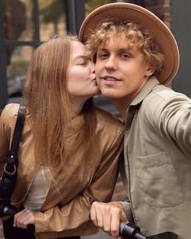Frau, die seinen freund küsst, während selfie auf elektrorollern nimmt