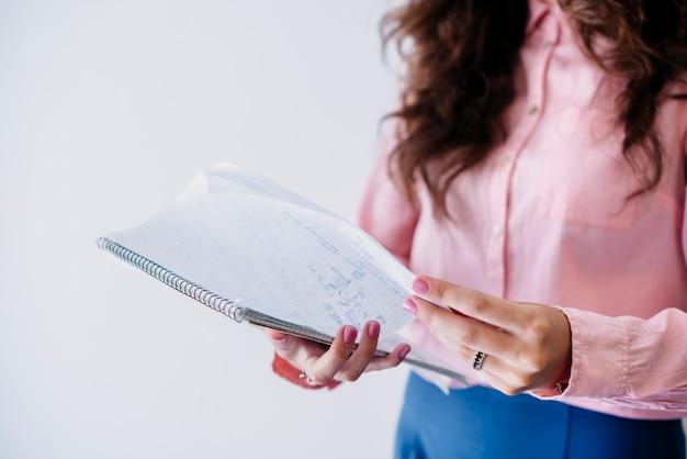 Frau, die seite im notizbuch im studio leicht schlägt