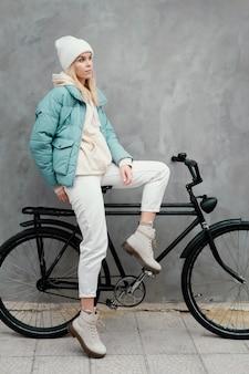 Frau, die seitlich auf ihrem fahrrad sitzt
