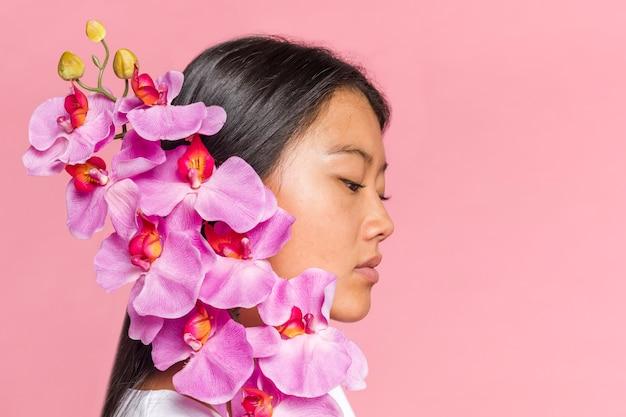 Frau, die seitlich ihr gesicht mit den orchideenblumenblättern bedeckt