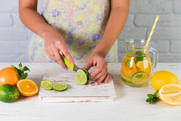 Frau, die selbst gemachte limonade zubereitet