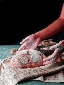 Frau, die selbst gemachtes rundes brot mit mehl auf die hände und auf die oberseite des brotes auf ein rustikales tuch setzt.