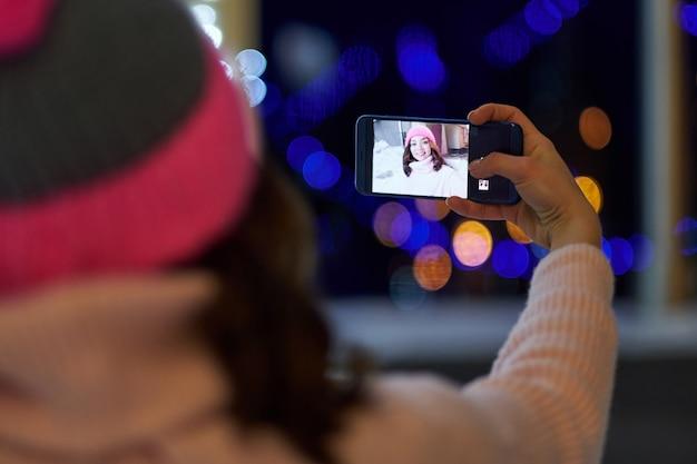 Frau, die selfie auf hintergrund der nachtwinterstadt nimmt. dame, die klassische stilvolle winterstrickjacke und -handschuhe trägt.