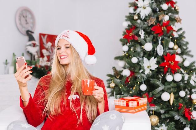 Frau, die selfie auf weihnachtsbaumhintergrund nimmt