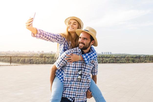 Frau, die selfie beim haben von huckepack auf der rückseite ihres freundes nimmt