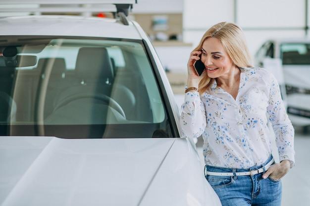 Frau, die selfie durch das auto in einem autoausstellungsraum tut