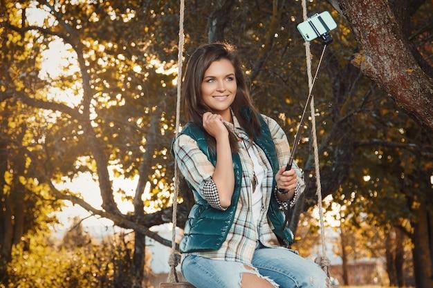 Frau, die selfie im herbstpark nimmt